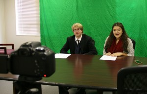 Mackenzie Mitchell and Jazmine Morfin are pictured recording a promotional video for the food drive. Through the use of a green screen, Mackenzie was able to integrate Hunger Games-style backgrounds for the version that was shown to students each week.