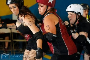 V Town Darlings Sarah Gasca and Christina Chandler lock in their opponent during a recent game with the Pacific Coast Recycled Rollers. Photo by David Costa.