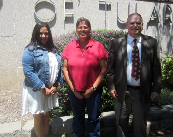 Julia Jimenez, her mother, and Paul Grenseman in front of the Tulare County Courthouse.