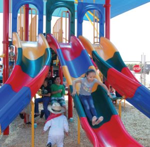 Five-year-old Darlene slides down the new playground equipment at the Plainview Neighborhood Park grand opening in June.