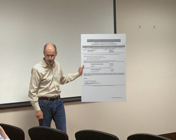 Michael Lampe, a Visalia attorney pursuing multiple cases against the Tulare Local Healthcare District, holds up a document showing the TLHCD authorized the disbursement of its $800,000 line of credit to a pharmaceutical company. Tony Maldonado/Valley Voice
